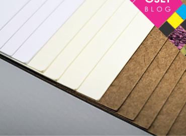 Papéis couché e kraft empilhados. Na imagem existe o nome do post: Quais são os tipos de papel e seus usos?